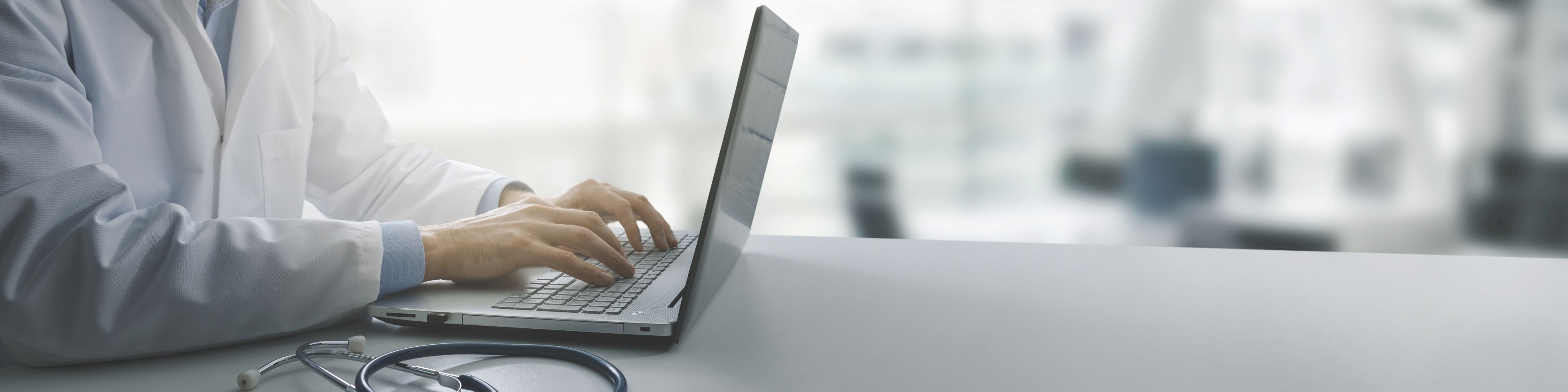 Male doctor typing on laptop at a desk.