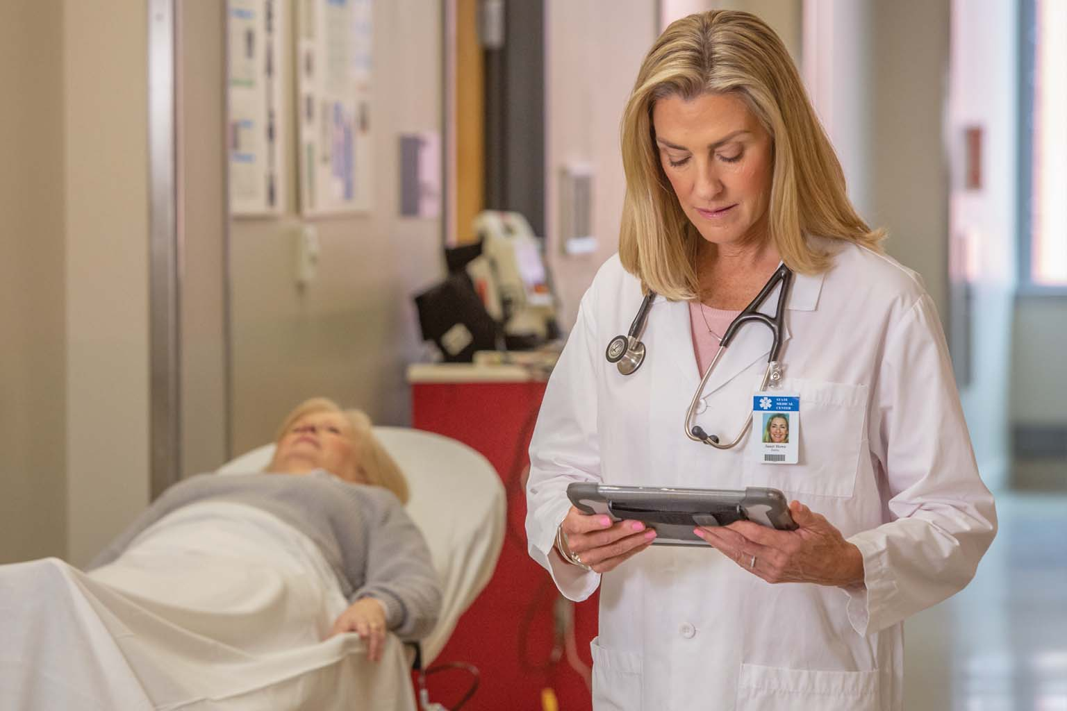doctor using tablet in hospital hallway in front of patient on gurney