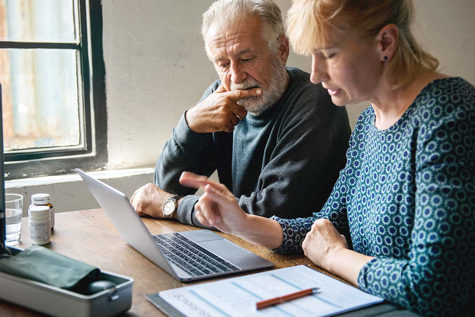 two people at kitchen table reviewing medication and information on laptop