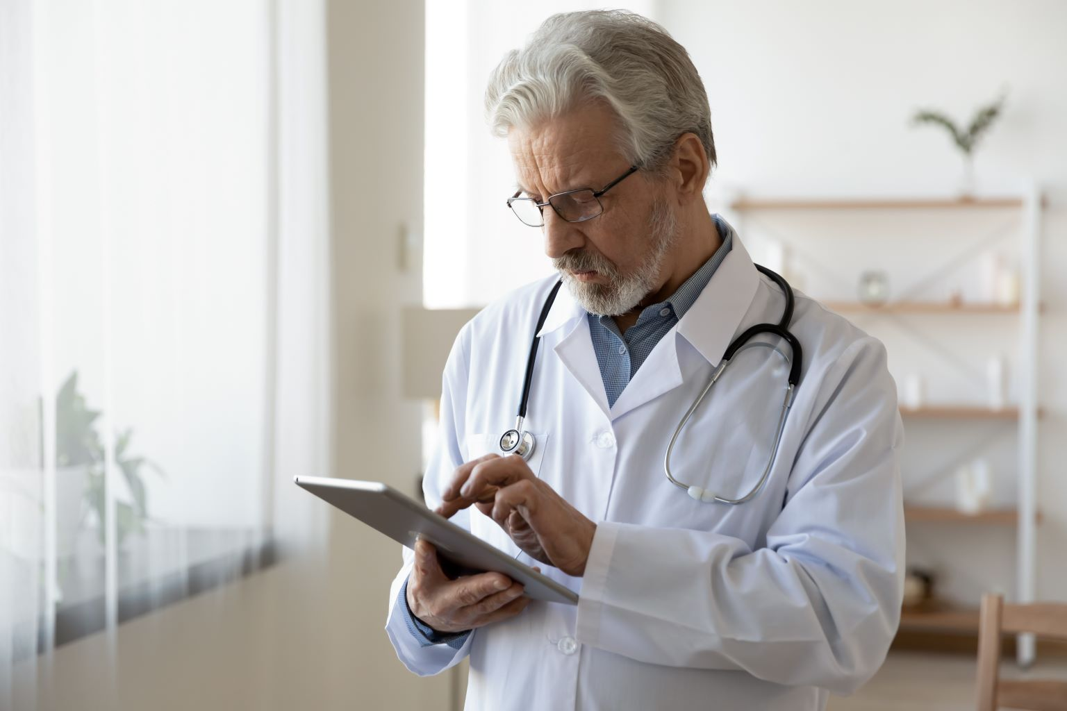 Male doctor holding a tablet in an office.