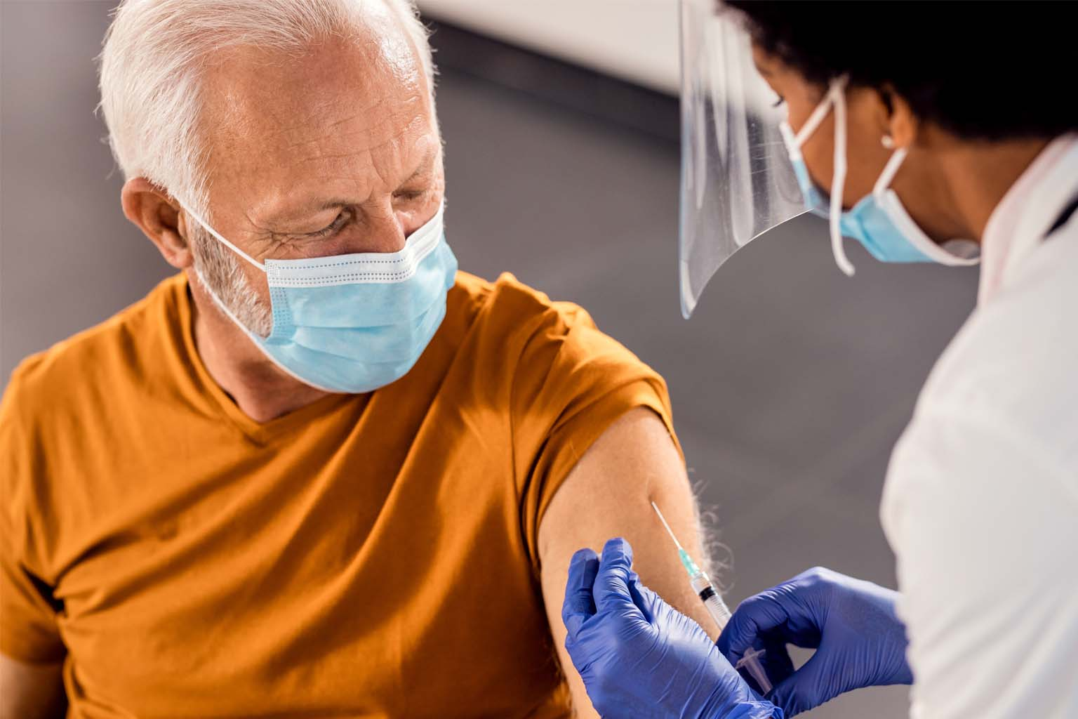 mature male receiving Covid vaccine