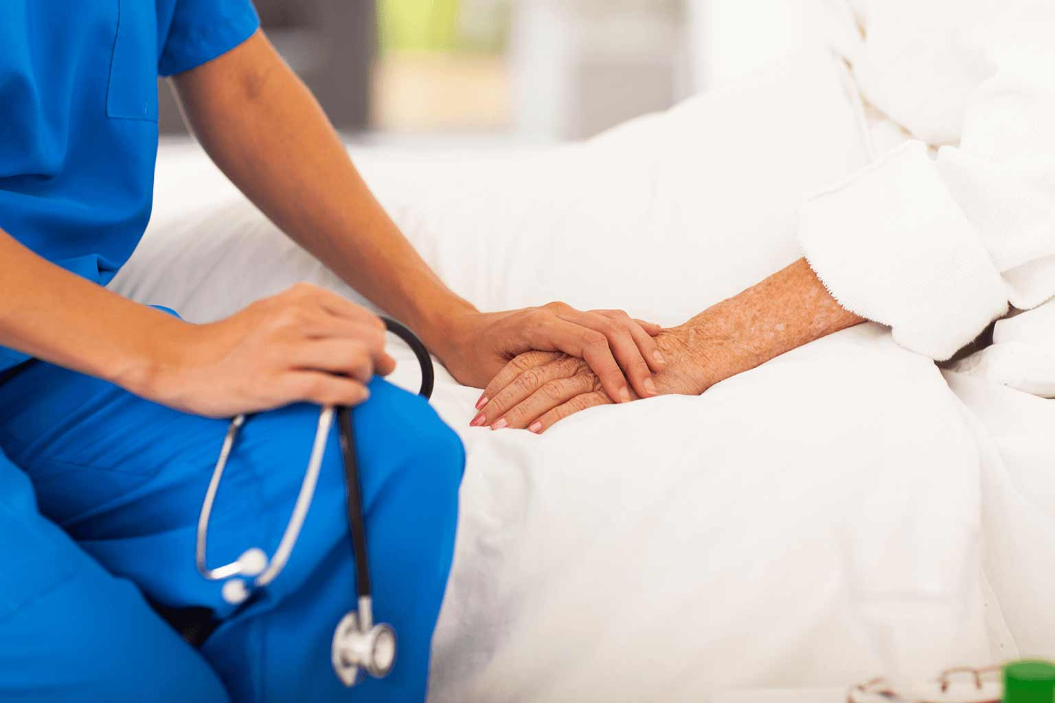 female-nurse-holding-patients-hand-while-in-hospital-bed
